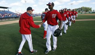 Washington Nationals manager Matt Williams, left, celebrates with center fielder Michael Taylor and others after an exhibition baseball game against the Houston Astros, Friday, March 7, 2014, in Viera, Fla. The Nationals won 8-5. (AP Photo/Alex Brandon)