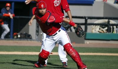 Washington Nationals catcher Jhonatan Solano prepares to throw to first for the out after fielding a bunt by Houston Astros' Marwin Gonzalez in the eighth inning of a spring exhibition baseball game, Friday, March 7, 2014, in Viera, Fla. The Nationals won 8-5. (AP Photo/Alex Brandon)