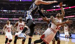 Memphis Grizzlies forward Mike Miller, front left, blocks the shot of Chicago Bulls guard D.J. Augustin (14) as Bulls' Jimmy Butler (21) and Nazr Mohammed (48) watch during the first half of an NBA basketball game on Friday, March 7, 2014, in Chicago. (AP Photo/Charles Rex Arbogast)