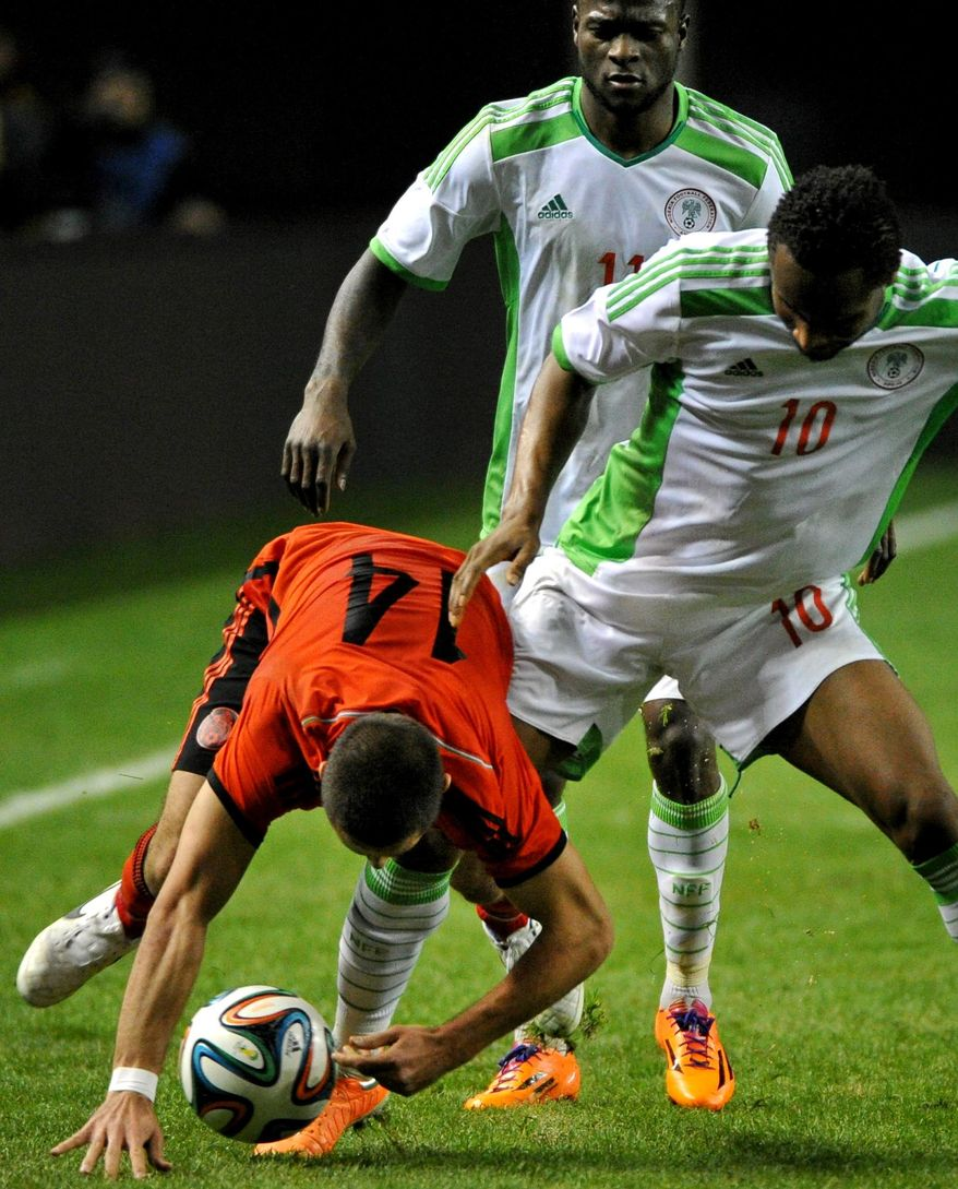 Nigeria's John Obi Mikel (10) trips up Mexico's Javier Hernandez (14) as Nigeria's Victor Moses (11) watches during the first half of an international friendly soccer match Wednesday, March 5, 2014, in Atlanta. (AP Photo/David Tulis)