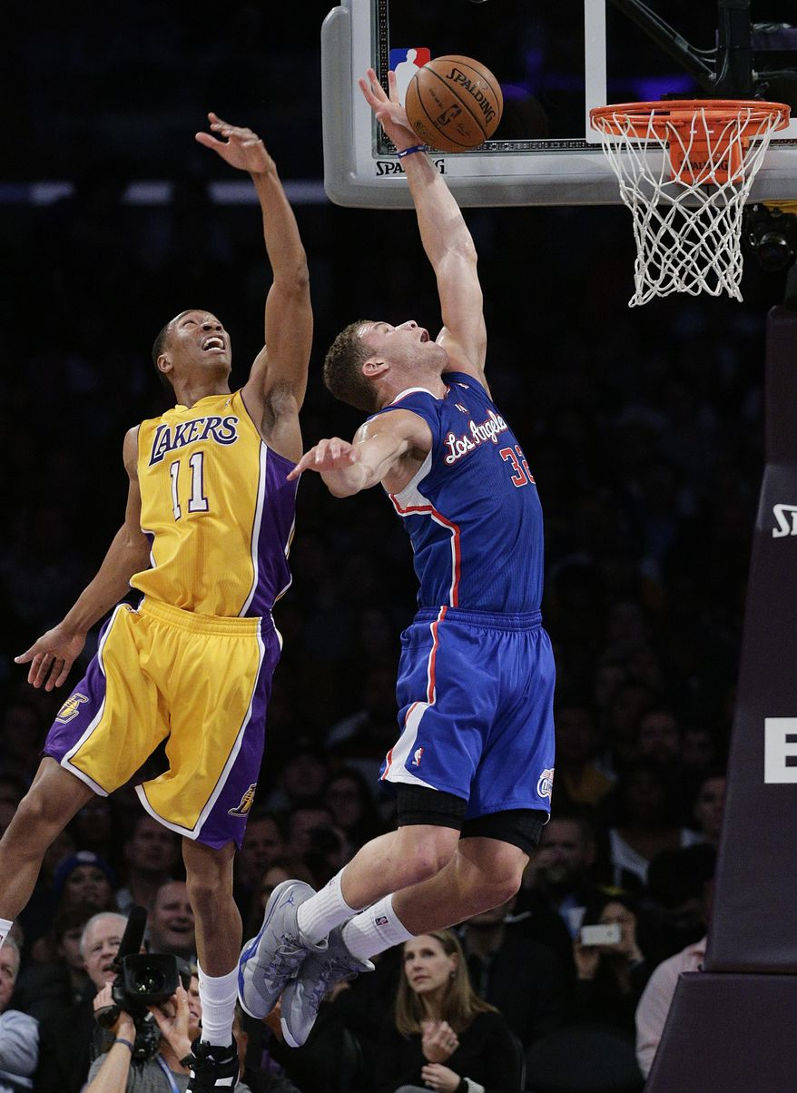 Los Angeles Clippers' Blake Griffin, center, goes up for a basket against Los Angeles Lakers' Wesley Johnson during the first half of an NBA basketball game on Thursday, March 6, 2014, in Los Angeles. (AP Photo/Jae C. Hong)