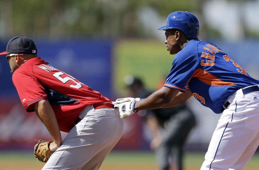 New York Mets' Curtis Granderson, right, jokingly grabs the belt loop of St. Louis Cardinals first baseman Scott Moore while taking a lead off first during the fourth inning of an exhibition spring training baseball game Friday, March 7, 2014, in Port St. Lucie, Fla. (AP Photo/Jeff Roberson)