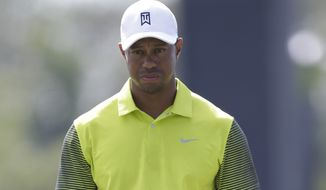 Tiger Woods prepares to hit on the 17th hole during the first round of the Cadillac Championship golf tournament Friday, March 7, 2014, in Doral, Fla. A severe thunderstorm delayed first round play on Thursday. (AP Photo/Wilfredo Lee)