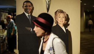 Dr. Colleen Copelan, foreground, walks past the cardboard cutouts of President Barack Obama, left, and former first lady Hillary Rodham Clinton at the California Democrats State Convention on Friday, March 7, 2014, in Los Angeles. Even in an election year that appears favorable for national Republicans, California Democrats are confident they will retain their iron grip on state leadership and possibly enrich their share of House seats in Washington. (AP Photo/Jae C. Hong)