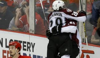 Colorado Avalanche's Nathan MacKinnon  (29) lands in the arms of Colorado Avalanche's Andre Benoit (61) after Benoit's game winning goal during overtime of an NHL hockey game against the Detroit Red Wings Thursday, March 6, 2014, in Detroit. MacKinnon assisted on the goal that defeated the Red Wings 3-2. (AP Photo/Duane Burleson)