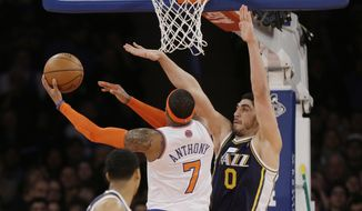 Utah Jazz's Enes Kanter (0) defends New York Knicks' Carmelo Anthony (7) during the first half of an NBA basketball game on Friday, March 7, 2014, in New York. (AP Photo/Frank Franklin II)