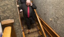 """Toronto Mayor Rob Ford speaks on the phone as he leaves the media preview for the Canadian launch of the """"Dressing for Downton: Costumes from Downton Abbey"""" exhibit at the Toronto Spadina Museum on Friday, March 7, 2014, in Toronto. (AP Photo/The Canadian Press, Michelle Siu)"""