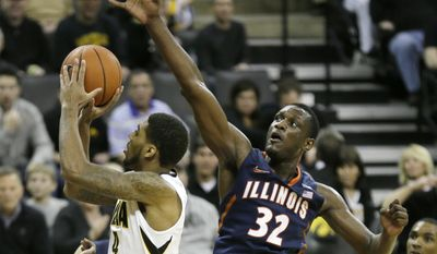 Illinois center Nnanna Egwu, right, tries to block a shot by Iowa guard Devyn Marble during the second half of an NCAA college basketball game on Saturday, March 8, 2014, in Iowa City, Iowa. (AP Photo/Charlie Neibergall)