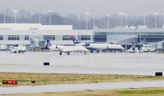 A United Express jet operated by ExpressJet pulls into the terminal after landing in rain on the main runway at Birmingham-Shuttlesworth International Airport in Birmingham, Ala., on Thursday, March 6, 2014. (AP Photo/Jay Reeves) ** FILE **