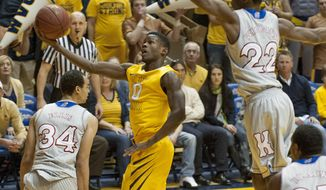West Virginia's Eron Harris, left, drives by Kansas' Andrew Wiggins during the first half of an NCAA college basketball game Saturday, March 8, 2014, in Morgantown, W.Va. (AP Photo/Andrew Ferguson)