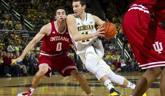Indiana forward Will Sheehey (0) defends against Michigan guard Nik Stauskas (11) in the first half of an NCAA college basketball game in Ann Arbor, Mich., Saturday, March 8, 2014. (AP Photo/Tony Ding)