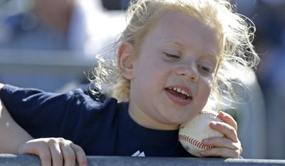 Callie Kemble, 5, of North Port, Fla., reacts after Tampa Bay Rays first base coach George Hendrick gave her a baseball during an exhibition baseball game against the Pittsburgh Pirates in Port Charlotte, Fla., Saturday, March 8, 2014. (AP Photo/Gerald Herbert)