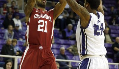 Oklahoma forward Cameron Cook (21) takes a shot as TCU guard Jarvis Ray (22) defends in the first half of an NCAA college basketball game Saturday, March 8, 2014, in Fort Worth, Texas. (AP Photo/Sharon Ellman)