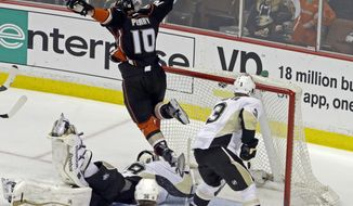 Anaheim Ducks right winger Corey Perry (10) leaps over Pittsburgh Penguins goalie Marc-Andre Fleury (29) as Perry scores a goal during the first period of an NHL hockey game in Anaheim, Calif., Friday, March 7, 2014. (AP Photo/Reed Saxon)