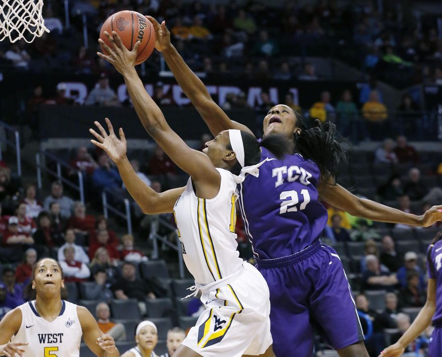 TCU center Latricia Lovings (21) reaches in to block a shot by West Virginia guard Darius Faulk (12) in the first half of an NCAA college basketball game in the quarterfinals of the Big 12 Conference women's tournament in Oklahoma City, Saturday, March 8, 2014. (AP Photo/Sue Ogrocki)