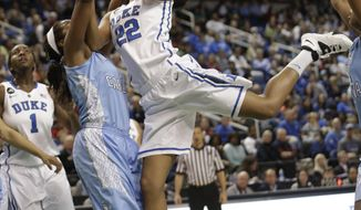 Duke's Oderah Chidom, right, tries to shoot over North Carolina's Brittany Rountree, left, during the first half of an NCAA college basketball semi-final game at the Atlantic Coast Conference tournament in Greensboro, N.C., Saturday, March 8, 2014. (AP Photo/Chuck Burton)