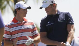 Rory McIlroy, left, of Northern Ireland, and Jamie Donaldson of Wales, talk before hitting from the third tee during the third round of the Cadillac Championship golf tournament Saturday, March 8, 2014, in Doral, Fla. (AP Photo/Marta Lavandier)