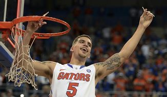 Florida guard Scottie Wilbekin (5) holds up a piece of the net after the Gators became the first team in Southeastern Conference history to go 18-0 in league pla, Saturday, March 8, 2014 in Gainesville, Fla.    Florida defeated Kentucky 84-65 Saturday in an NCAA college basketball game. (AP Photo/Phil Sandlin)