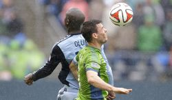 Seattle Sounders' Brad Evans, right, heads the ball next to Sporting Kansas City's Lawrence Olum, left, in the first half of an MLS soccer match, Saturday, March 8, 2014, in Seattle. (AP Photo/Ted S. Warren)
