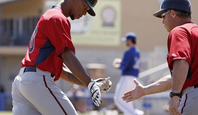 Minnesota Twins third base coach Joe Vavra, right, congratulates Byron Buxton (70) after Buxton hit a solo home run off Toronto Blue Jays starting pitcher Drew Hutchison, center, during a spring training baseball game Saturday, March 8, 2014, in Dunedin, Fla. (AP Photo/Kathy Willens)