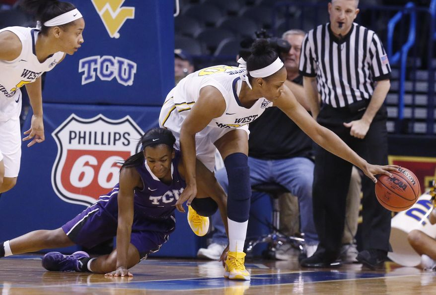 West Virginia center Asya Bussie (20) reaches over TCU guard Zahna Medley (14) for a loose ball in the first half of an NCAA college basketball game in the quarterfinals of the Big 12 Conference women's tournament in Oklahoma City, Saturday, March 8, 2014.  (AP Photo/Sue Ogrocki)