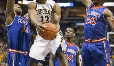 Marquette's Derrick Wilson (12) drives and makes a pass between St. Johns' Chris Obekpa, left, and Rysheed Jordan during the first half of an NCAA college basketball game Saturday, March 8, 2014, in Milwaukee. (AP Photo/Tom Lynn)
