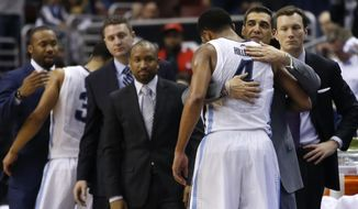 Villanova's Darrun Hilliard II (4) gets a hug from head coach Jay Wright after being pulled in final minutes of an NCAA college basketball game against Georgetown, Saturday, March 8, 2014, in Philadelphia. Villanova won 77-59. (AP Photo/Matt Slocum)