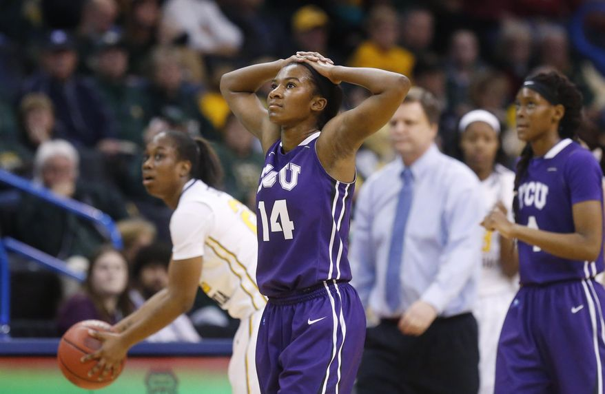 TCU guard Zahna Medley (14) walks off the court past West Virginia guard Linda Stepney (22) as the clock winds down in an NCAA college basketball game in the quarterfinals of the Big 12 Conference women's tournament in Oklahoma City, Saturday, March 8, 2014. West Virginia won 67-59. (AP Photo/Sue Ogrocki)