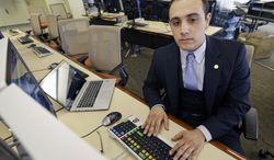 Twenty-three-year-old Fady Al-Banna works at a computer station in the business school at Wright State University, Friday, March 7, 2014, in Dayton, Ohio. Al-Banna's family left Iraq in 2007 after his father had a harrowing escape after two men abducted him in his car at gunpoint. Al-Banna is now a senior and the director of international affairs for student government at Wright State. He is also on a dean of students advisory board. (AP Photo/Al Behrman)