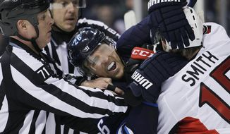 Referees attempt to pull apart Winnipeg Jets' Blake Wheeler (26) and Ottawa Senators' Zack Smith (15) during the second period of an NHL hockey game, Saturday, March 8, 2014 in Winnipeg, Manitoba. (AP Photo/The Canadian Press, John Woods)