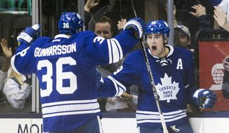 Toronto Maple Leafs' Joffrey Lupul, right, turns to celebrate with teammate Carl Gunnarsson after scoring the game winning goal against Philadelphia Flyers during overtime of an NHL hockey game, Saturday, March 8, 2014 in Toronto. (AP Photo/The Canadian Press, Chris Young)