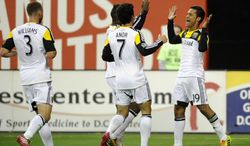 Columbus Crew's Jairo Arrieta (19) celebrates his goal with Bernardo Anor (7) and Josh Williams (3) during the first half of an MLS soccer game against D.C. United, Saturday, March 8, 2014, in Washington. (AP Photo/Nick Wass)