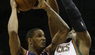 Washington Wizards' Trevor Ariza (1) shoots against Milwaukee Bucks' Jeff Adrien during the first half of an NBA basketball game on Saturday, March 8, 2014, in Milwaukee. (AP Photo/Jeffrey Phelps)