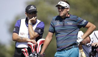 Ian Poulter of England, right, waits his turn with caddie Terry Mundy on the fourth tee during the second round of the Cadillac Championship golf tournament Friday, March 7, 2014, in Doral, Fla. (AP Photo/Wilfredo Lee)
