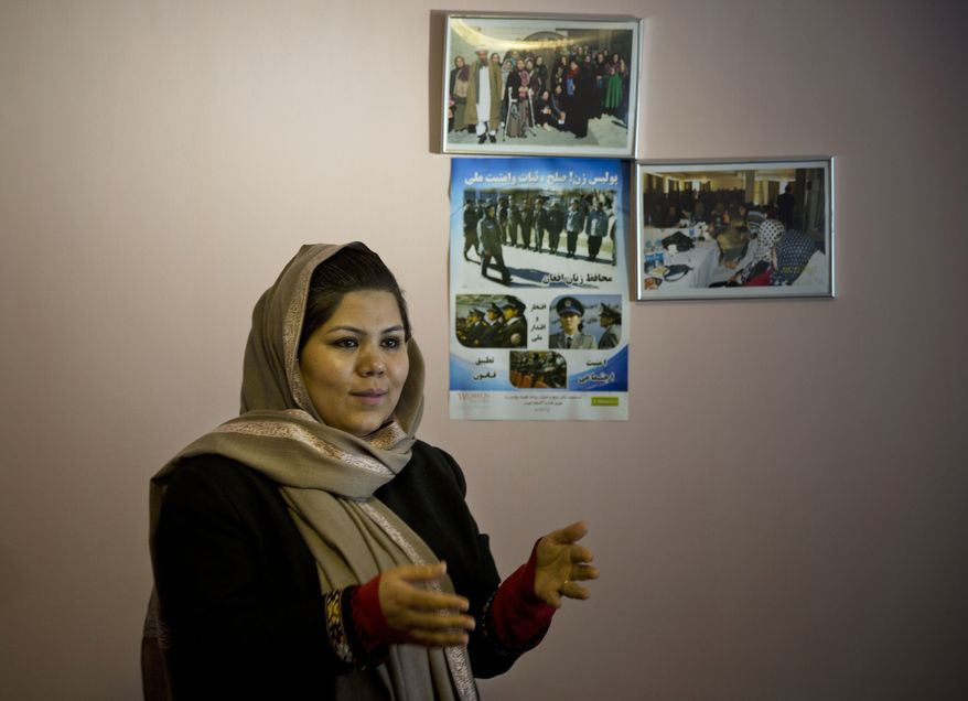 In this Wednesday, March 5, 2014 photo, prominent Afghan women's rights activist Wazhma Frogh stands next to pictures of female Afghan police officers she trains, in her office in Kabul, Afghanistan. A gender and development specialist and human rights activist, Frogh says her experience characterizes the women's rights movement in her country- after 12 years, billions of dollars and countless words emanating from the West commiserating with Afghan women, the successes are fragile, the changes superficial and vulnerable.  (AP Photo/Anja Niedringhaus)