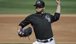 Colorado Rockies starting pitcher Brett Anderson throws against the Oakland Athletics during the second inning of a spring training baseball game in Scottsdale, Ariz., Saturday, March 8, 2014. (AP Photo/Chris Carlson)