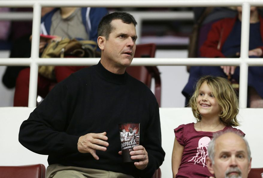 San Francisco 49ers coach Jim Harbaugh sits with his 5-year-old daughter, Addison, during halftime of Stanford's NCAA college basketball game against Utah on Saturday, March 8, 2014, in Stanford, Calif. (AP Photo/Eric Risberg)