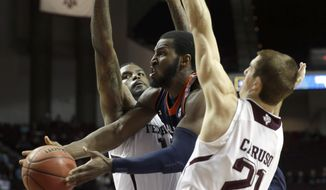 Auburn's KT Harrell, center, goes between Texas A&M defenders Alex Caruso (21) and Kourtney Roberson to pass the ball during the second half of an NCAA college basketball game Saturday, March 8, 2014, in College Station, Texas. Auburn won 69-64. (AP Photo/David J. Phillip)