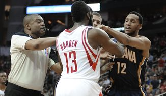 Referee Tony Brothers, left, tries to break up a confrontation between Houston Rockets' James Harden (13) and Indiana Pacers' Evan Turner (12) during the first half of an NBA basketball game Friday, March 7, 2014, in Houston. Both players received a technical foul. (AP Photo/Pat Sullivan)