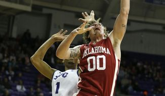 TCU center Karviar Shepherd (1) guards Oklahoma forward Ryan Spangler (00) in the first half of an NCAA college basketball game Saturday, March 8, 2014, in Fort Worth, Texas. (AP Photo/Sharon Ellman)