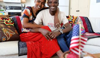 In this photo taken on Feb. 27, 2014, Argaw Oremo, along with his wife Workensh Nege Egoye who recently arrived in the United States recently from their homeland of Ethiopia, pose for a photograph in their home in Dubuque, Iowa.  Argaw won a immigration lottery slot to come to the US a few years ago and recently returned home after his wife was granted a visa to come to America and be with her husband. (AP Photo/The Telegraph Herald, Dave Kettering)  MAGS OUT, TV OUT