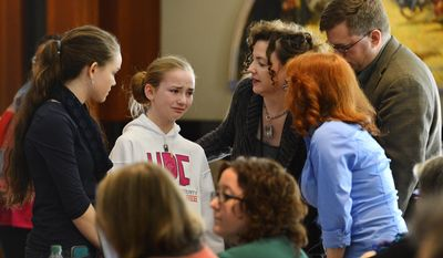 """Head judge Kaite Stover, second from right, informs the Sophia Hoffman, second from left, and her family that her misspelling of the word """"stifling"""" in the 28th round of the Jackson County Spelling Bee was confirmed at the Central Library in Kansas City, Mo. Two weeks ago, the bee ran out of words after the two eliminated 23 other contestants and went another 47 rounds against each other. Kush Sharma won the competition after spelling """"definition"""" correctly in the 29th round Saturday. (AP Photo/The Kansas City Star, Jill Toyoshiba)"""