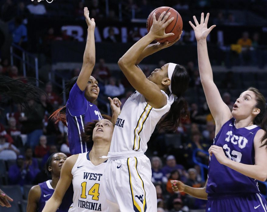 West Virginia guard Christal Caldwell (1) shoots between TCU guard Natalie Ventress, left, and guard Donielle Breaux (33) and West Virginia's Jess Harlee (14) in the first half of an NCAA college basketball game in the quarterfinals of the Big 12 Conference women's tournament in Oklahoma City, Saturday, March 8, 2014.  (AP Photo/Sue Ogrocki)
