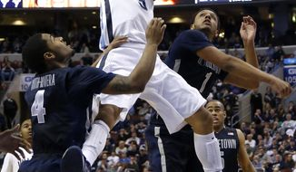 Villanova's Josh Hart, center, goes up for a shot as Georgetown's D'Vauntes Smith-Rivera, left, and Reggie Cameron defend during the first half of an NCAA college basketball game, Saturday, March 8, 2014, in Philadelphia. (AP Photo/Matt Slocum)