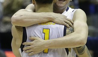 California's Justin Cobbs (1) is embraced by Sam Singer at the end of an NCAA college basketball game against Colorado, Saturday, March 8, 2014, in Berkeley, Calif. (AP Photo/Ben Margot)