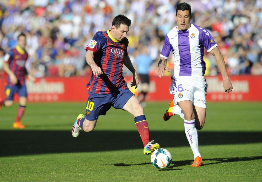 Barcelona's Lionel Messi from Argentina, left, and Valladolid's defender Jesus Rueda challenge for the ball during a Spanish La Liga soccer match at the Jose Zorrilla stadium in Valladolid, Spain, Saturday March 8, 2014. (AP Photo/Israel L. Murillo)