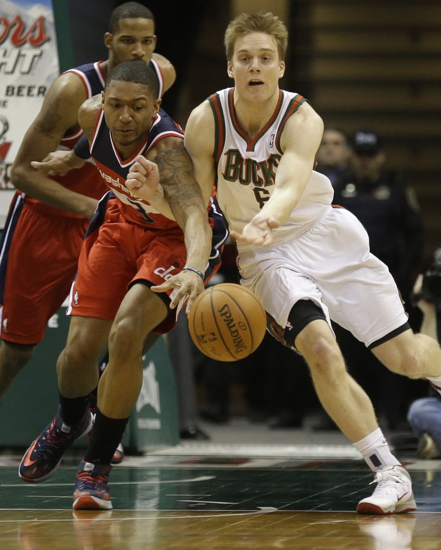 Washington Wizards' Bradley Beal, left, and Milwaukee Bucks' Nate Wolters reach for a loose ball during the first half of an NBA basketball game on Saturday, March 8, 2014, in Milwaukee. (AP Photo/Jeffrey Phelps)