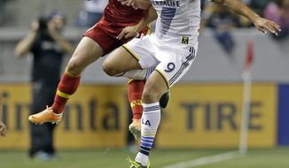 Real Salt Lake midfielder Ned Grabavoy, left, and Los Angeles Galaxy forward Samuel go for a head ball during the first half of an MLS soccer game in Carson, Calif., Saturday, March 8, 2014. (AP Photo/Reed Saxon)