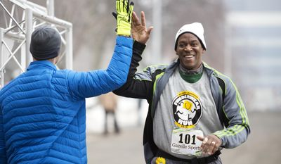 Michael Robinson high-fives Matt Lauria as he crosses the finish line during LaughFest's FUNderwear 5K run in Grand Rapids, Mich. Sunday, March 9, 2014. (AP Photo/The Grand Rapids Press, Lauren Petracca)