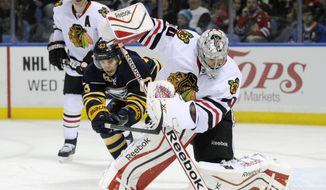 Buffalo Sabres center Tyler Ennis (63) hooks Chicago Black Hawks goaltender Corey Crawford who handles the puck during the first period of an NHL hockey game in Buffalo, N.Y., Sunday, March 9, 2014. (AP Photo/Gary Wiepert)